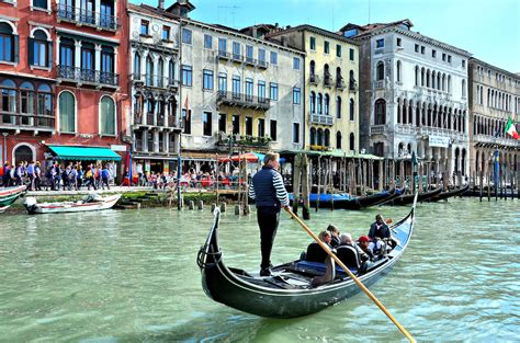 Venice Gondola Or Boat by Gondola Rowing Along Grand Canal In Venice Italy