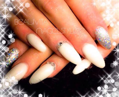 witte acryl nagels met een zilverglitter op duim en
