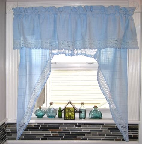 white wooden kitchen window with blue curtain and valance