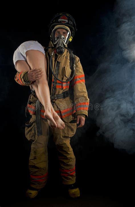 Fireman saving a victim stock image. Image of fitness