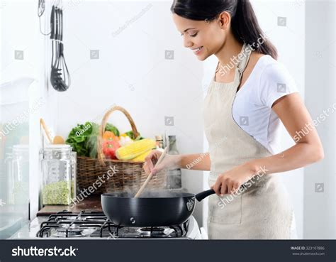 cooking in the kitchen standing by stove kitchen cooking stock photo