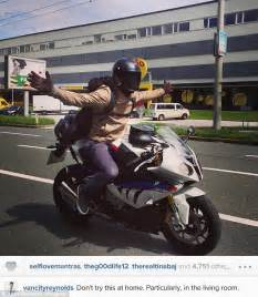 Ryan Reynolds rides hands free on a motorcycle in ...