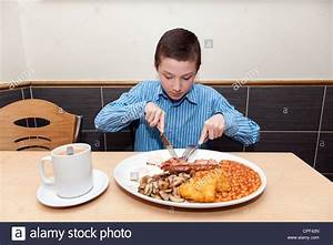 Young boy eating full English breakfast in a cafe, London ...