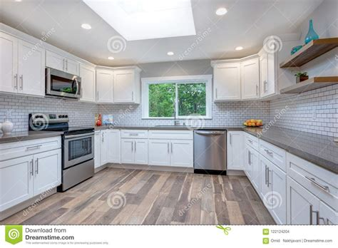 White Cupboards With Stainless Steel Appliances by Open Concept Kitchen Equipped With Stainless Steel