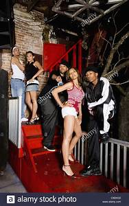 Group of young men and women in hip-hop fashion posing ...