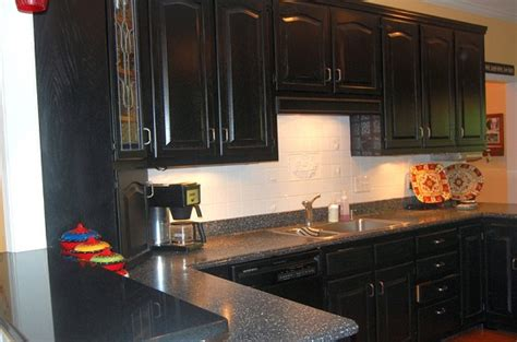distressed black cabinets with black granite countertops