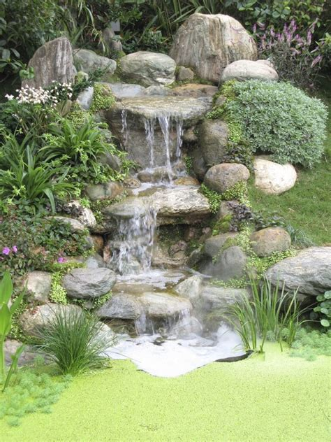 A Threetiered Stone Waterfall That Ends In A Tiny But