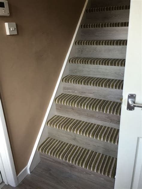 mixture of striped carpet and laminate stairs for a transition from upstairs to downstairs