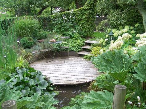 tuin met vijver vlonder en overkapping natuurlijke tuin met houten vlonder terras bij vijver