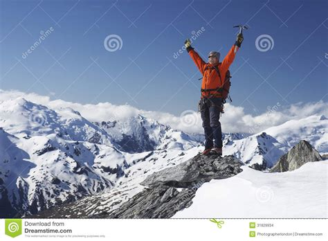 Mountain Climber With Arms Raised On Snowy Peak Stock