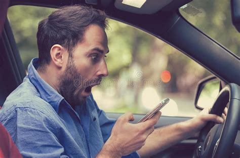 Man Sitting Inside Car With Mobile Phone Texting While