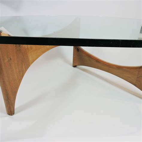 This coffee table is built from ash and walnut. Mid-Century Modern Glass and Wood Coffee Table at 1stdibs