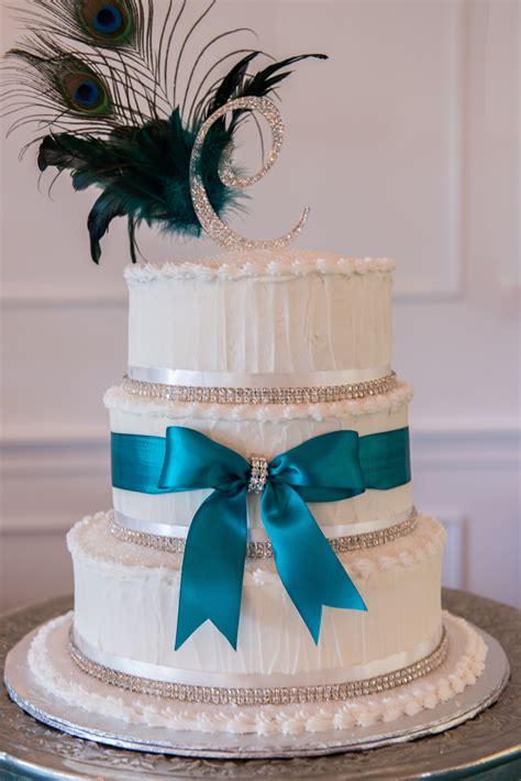 white wedding cake  turquoise ribbon  peacock