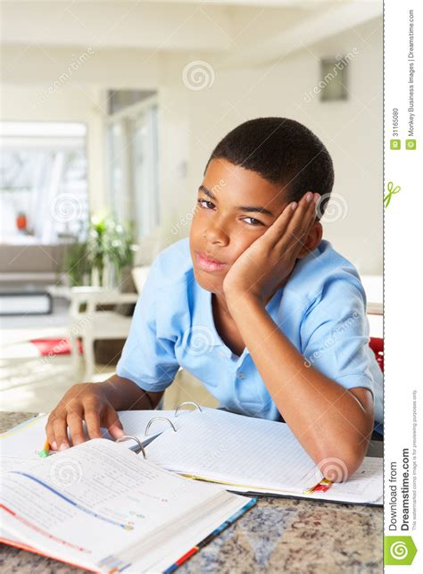 Fed Up Boy Doing Homework In Kitchen Stock Photo Image