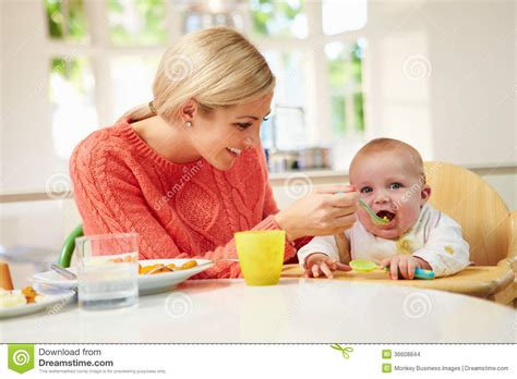 feeding baby sitting in high chair at mealtime