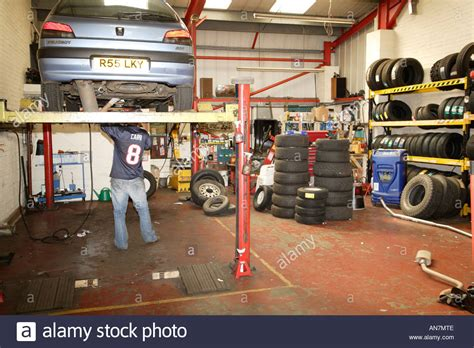 Mobile Garage Door Mechanic by Car Up On Hydraulic Lift At A Garage Mechanic Working