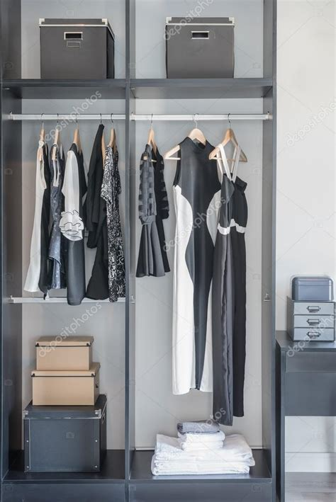 black and white clothes hanging in closet stock photo