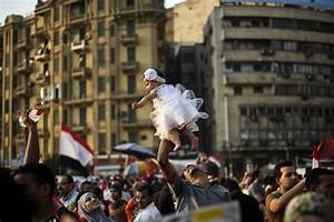 An Egyptian man holds his daughter aloft in Cairo's Tahrir ...