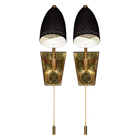 brass one light sconces with black shade and pull cord at