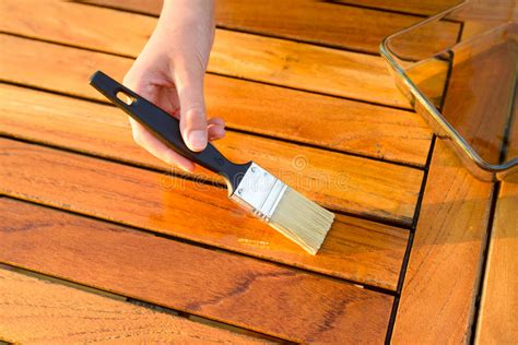 wood maintenance hand holding a brush applying varnish paint on a wooden garden table stock photo image of