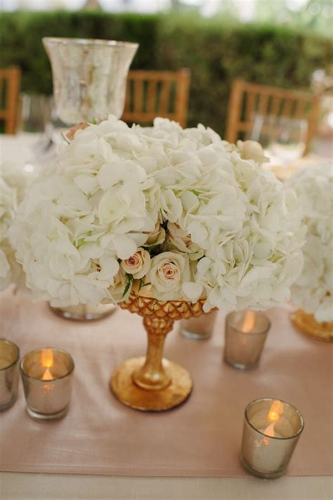 white and gold centerpieces some of the centerpieces will have a low gold gilded compote vase overflowing with cream