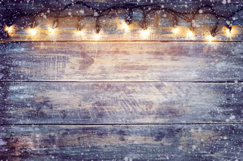 Christmas Lights Bulb With Snow On Wood Table. Merry