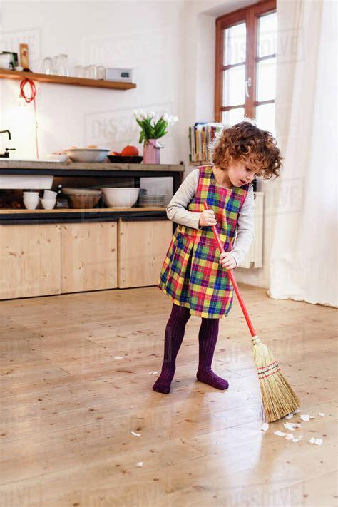 cute girl sweeping kitchen floor stock photo dissolve