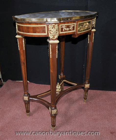 The tops of the legs and frieze having stylised cast metal patre and mounts. Pair French Empire Oval Side Tables Cocktail Table
