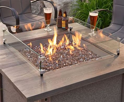 A wind guard enhances the look of the fire pit while it serves as a protective barrier confining the flame within the glass area. Square Fire Pit Wind Guards | Fine's Gas