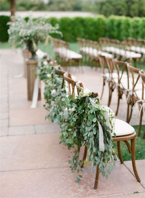 aisle chairs decorated  eucalyptus  ribbons