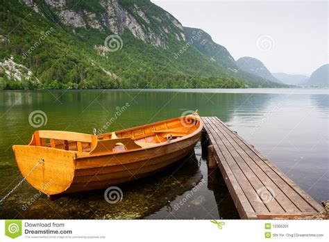 Boat Berth by Boat Berth By The Tranquil Lake Pier With Mountain Stock