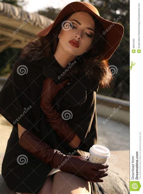 beautiful girl  elegant coat  hat drinking coffee