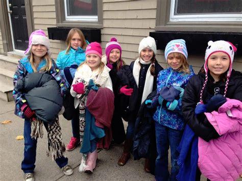kids  tying coats  street poles  homeless people