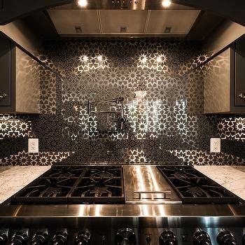 Gray Kitchen with Mirrored Flower Cooktop Backsplash