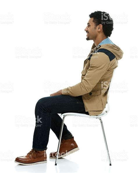 chaise assis smiling on chair and looking away stock photo