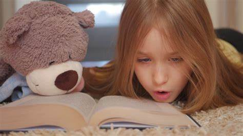 Cute happy little girl with teddy bear and reading book ...