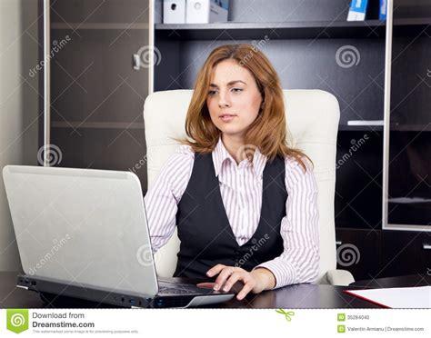 femme s asseyant dans le bureau dactylographiant sur l ordinateur portable photo stock