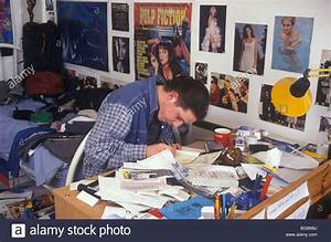 teenage boy doing his homework at his messy desk in his With boys homework desk