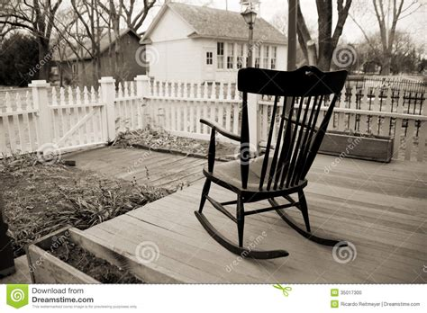 rocking chair  wooden porch  white picket fence
