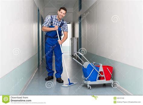 travailleur de sexe masculin heureux avec le couloir de bureau de nettoyage de balai photo stock
