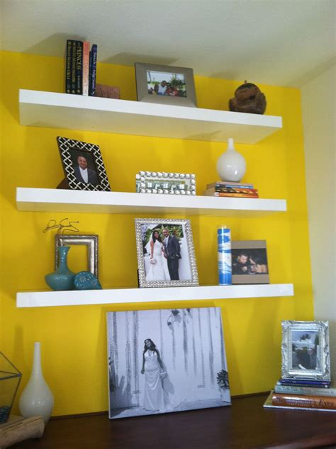yellow accent wall  floating shelves yellow accent