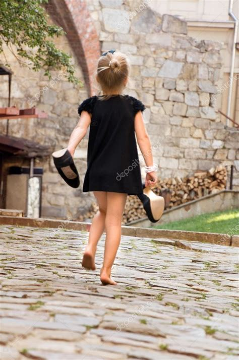 girl holding  shoes  runs  barefoot
