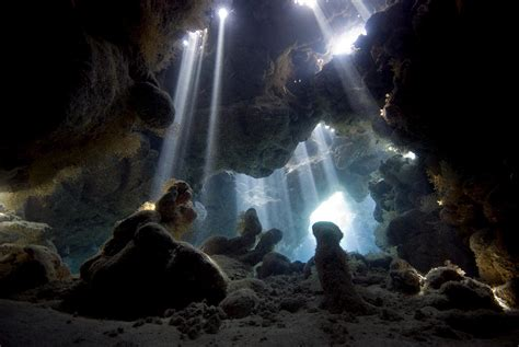 the cave and the light sun light breaking through into cave photograph by dray