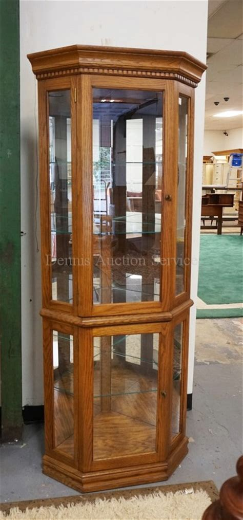 lighted oak corner curio cabinet with glass shelves and a mi