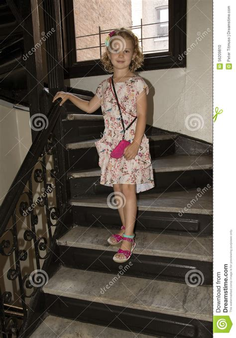 young girl walking  stairs holding  rail stock