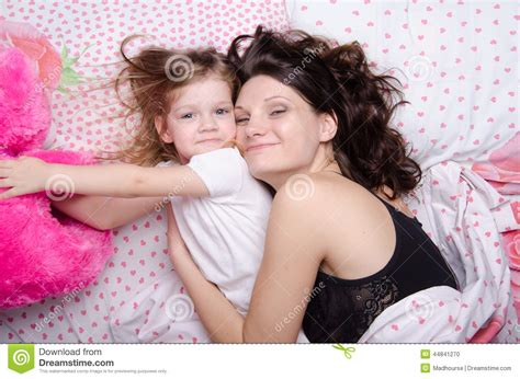 Daughter Reaches For A Soft Toy Lying With Her Mother