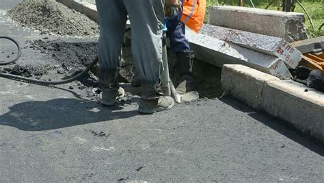 worker drilling concrete with compressor on the