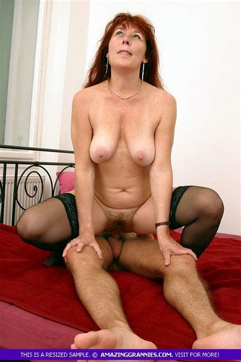 Redhead Granny With Big Breasts And Hairy Bush Is Riding On A Young Cock And Lets Him Fuck Her