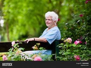 Happy Senior Lady Sitting On Wooden Image & Photo