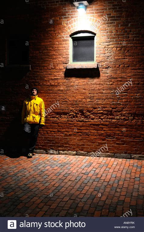 single man leaning on a red brick wall under a streetlight